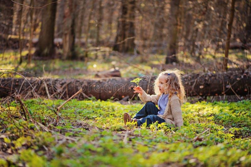 La fille mignonne d'enfant s'asseyant en vert part dans la forêt tôt de ressort image libre de droits