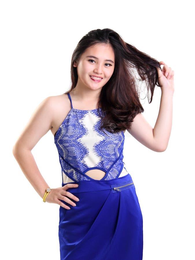 La fille mignonne dans la robe bleue joue avec ses cheveux photographie stock libre de droits