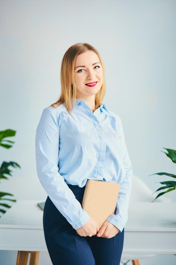 La fille mignonne dans le bureau se tient près de la table et de tenir le livre de métier Jeune femme dans l'appareil-photo bleu  photos stock