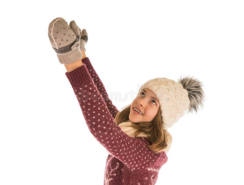 La fille mignonne dans le chandail, le chapeau, l'écharpe et des mitaines chauds met ses mains photo libre de droits