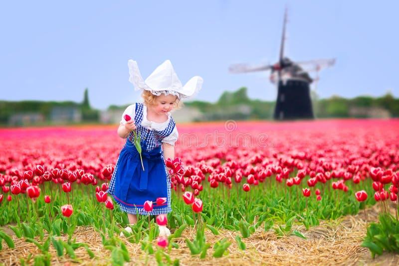 La fille mignonne dans le costume néerlandais dans les tulipes mettent en place avec le moulin à vent photographie stock libre de droits