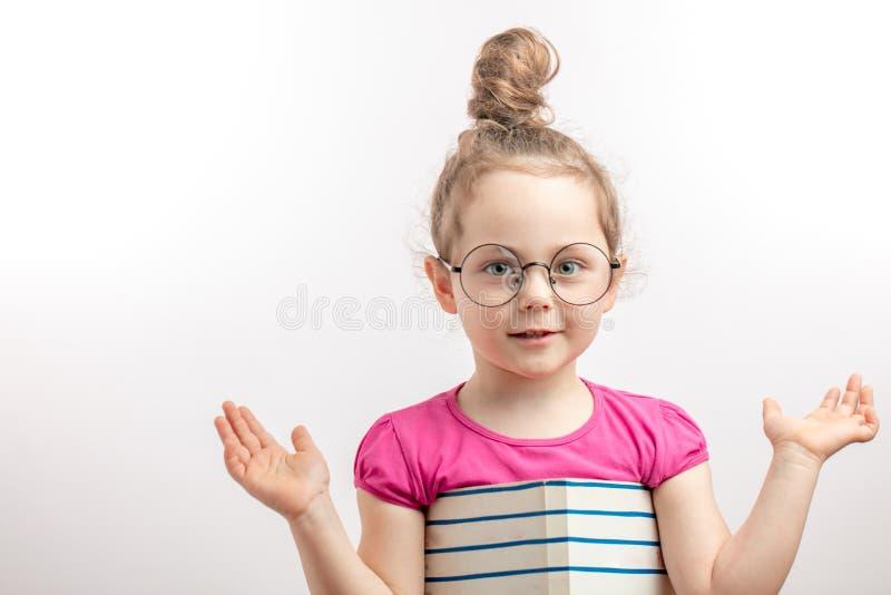 La fille mignonne de gingembre montre le tour avec le bloc-notes photos libres de droits