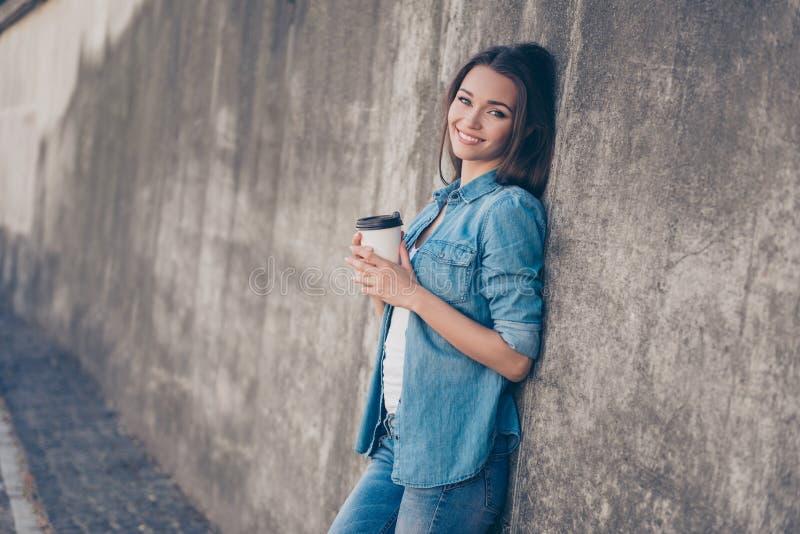 La fille mignonne de jeune brune rêveuse avec du charme boit du thé chaud près du mur en béton dehors Elle est somnolente et déco photo stock