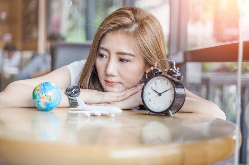 La fille mignonne de l'Asie regardant au globe et le réveil essayent de faire décembre images stock