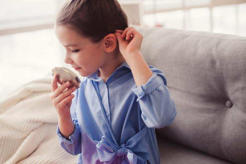 La fille mignonne de petit enfant avec le miroir et le cosmétique mettent en sac vérifier la coiffure à la maison photo stock
