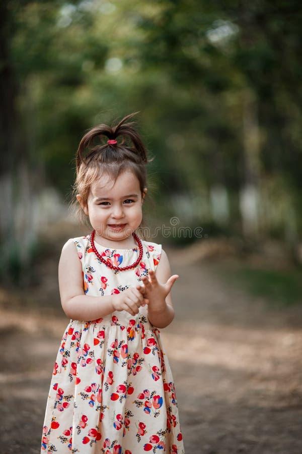 La fille mignonne et belle de peu dans une robe de cru fait des visages image stock