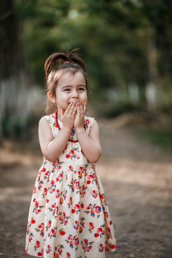 La fille mignonne et belle de peu dans une robe de cru fait des visages photo stock