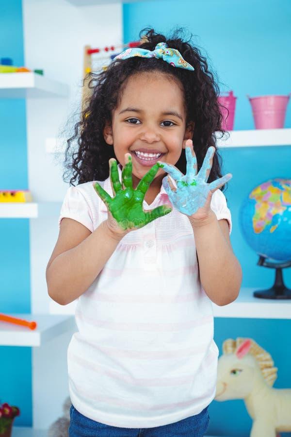 La fille mignonne lui montrant la peinture a couvert des mains image stock