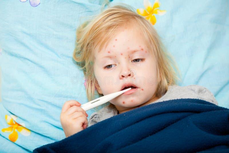 La fille mignonne malade mesure la température photographie stock