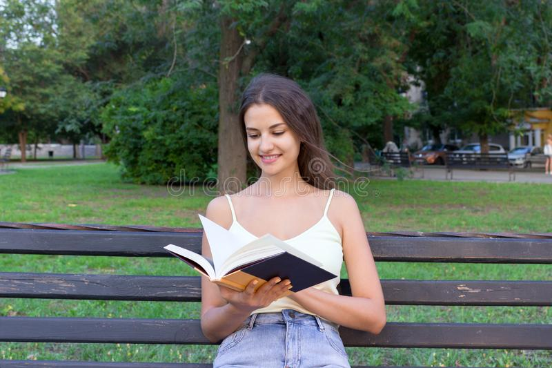 La fille mignonne recherche l'information dans un manuel se reposant sur le banc en parc La femme regarde par un livre et recherc photo libre de droits