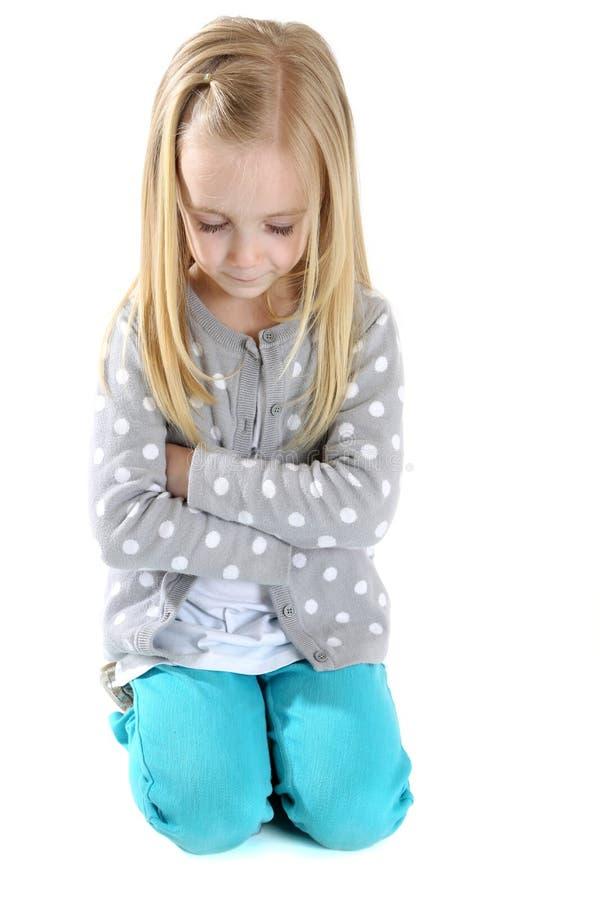 La fille mignonne se mettant à genoux en bas des bras a plié des yeux fermés pour prier photo stock