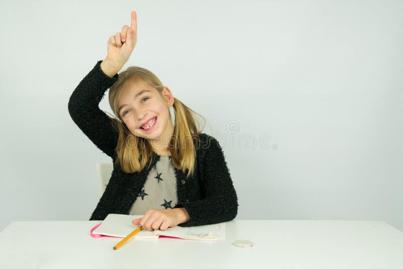 La fille mignonne soulève sa main dans la salle de classe images libres de droits