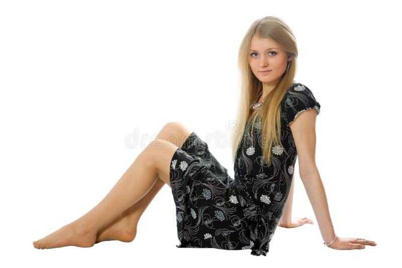 La fille mince attirante s'asseyent sur l'étage photographie stock