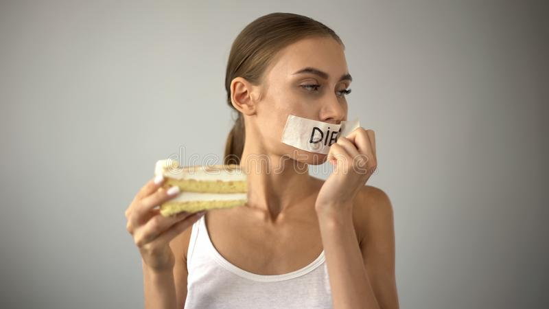 La fille mince choisissant de manger le gâteau, enlevant la bande de bouche, cessent de suivre un régime, tentation images stock