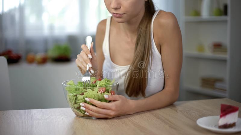 La fille mince choisit la salade au lieu du gâteau, alimentation équilibrée saine, autodiscipline photo libre de droits