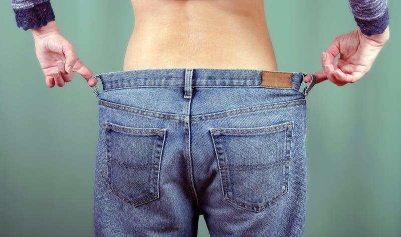La fille mince dans de grands jeans de retour regardent Une jeune femme montre une figure amincie Concept de perte de poids images libres de droits