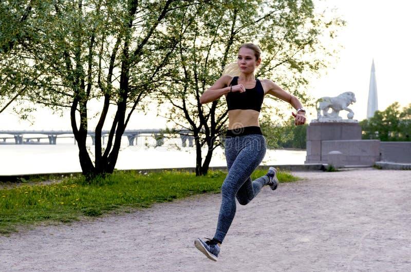 La fille mince dans des vêtements de sports court rapidement en parc le long du remblai de la rivière de Neva au coucher du solei photographie stock libre de droits