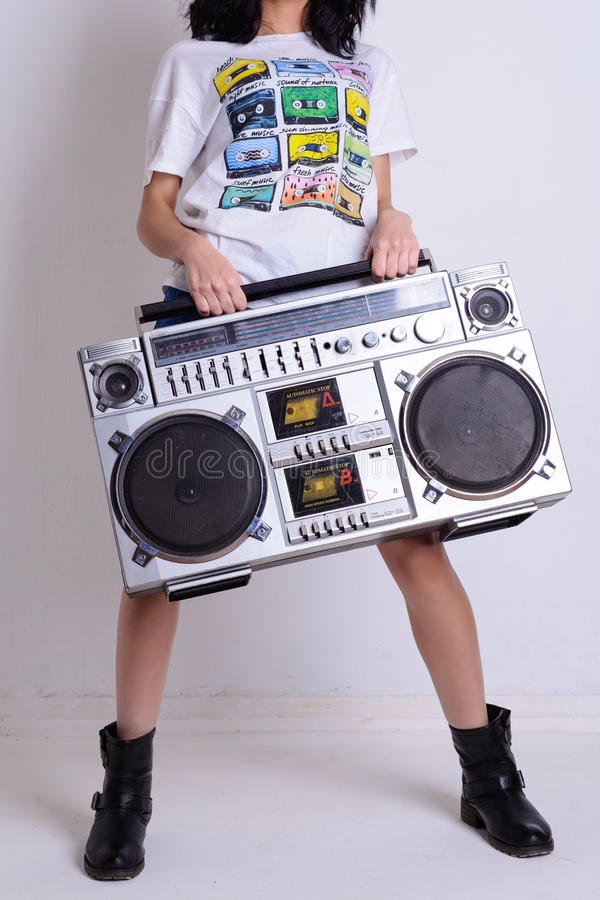 La fille mince dans une chemise blanche et les chaussures noires tiennent le vieux magnétophone à cassettes de bande images libres de droits