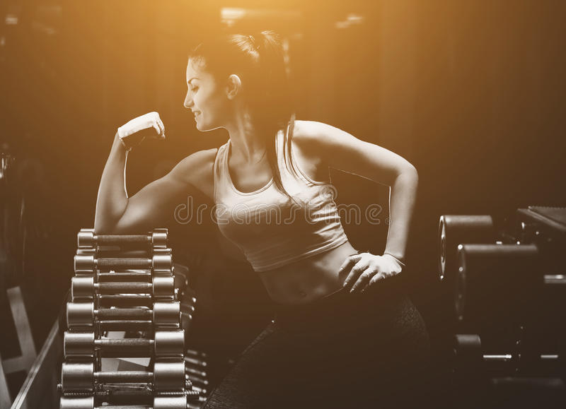 La fille mince de bodybuilder montre le biceps tout en s'exerçant dans le gymnase photos libres de droits