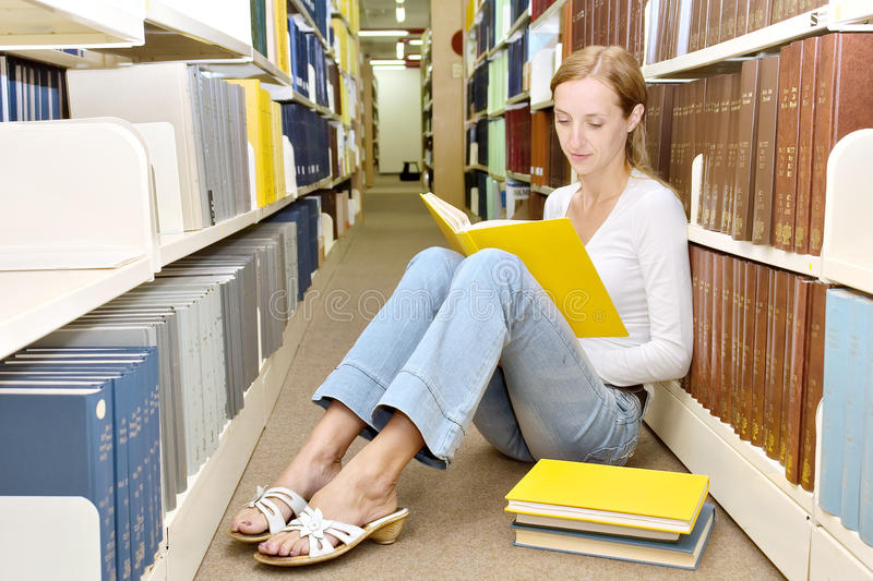 La fille mince s'assied sur l'étage dans la bibliothèque et affiche le livre photographie stock