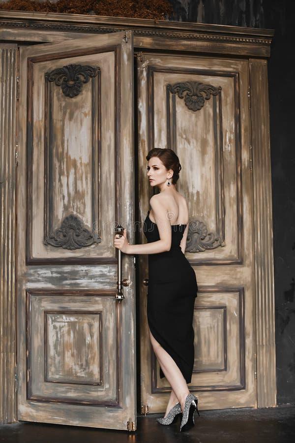 La fille modèle de brune sexy avec une coupe de cheveux à la mode et avec le maquillage lumineux, dans une longue robe noire à la photos libres de droits
