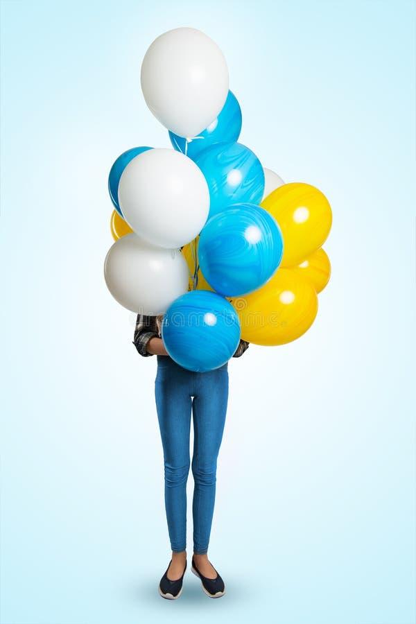 La fille modèle tient devant elle un groupe de ballons colorés Couvre le visage de ballons photos stock