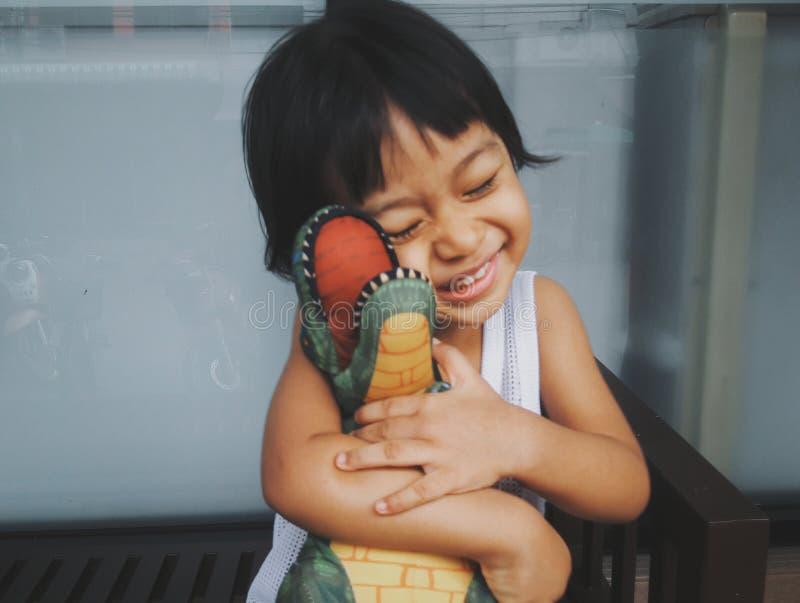 La fille molle de l'Asie d'enfant de style de cru de photo de foyer étreint la poupée de dinosaures heureusement Elle est concept images libres de droits