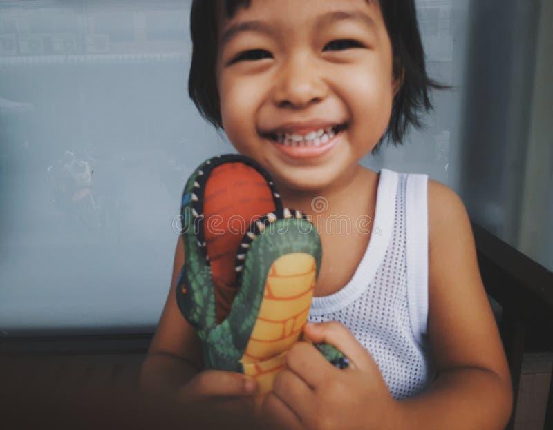La fille molle de l'Asie d'enfant de style de cru de photo de foyer étreint la poupée de dinosaures heureusement Elle est concept photos stock