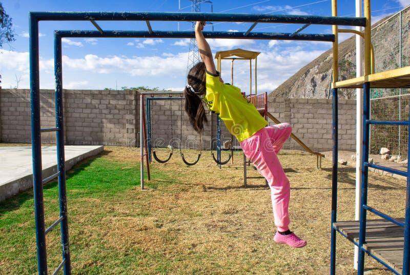 La fille monte la barre transversale À la cour de jeu photographie stock