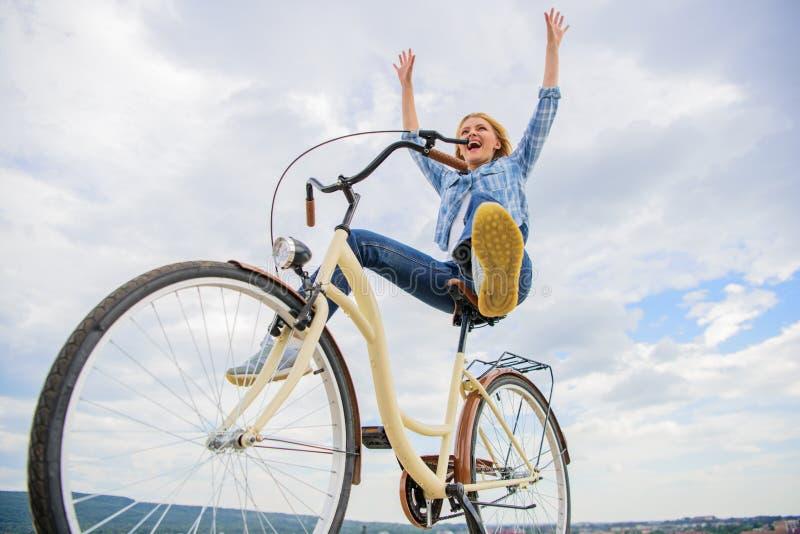 La fille monte le fond de ciel de bicyclette Liberté et plaisir La femme se sent libre tandis qu'ayez plaisir le recyclage La plu photographie stock libre de droits