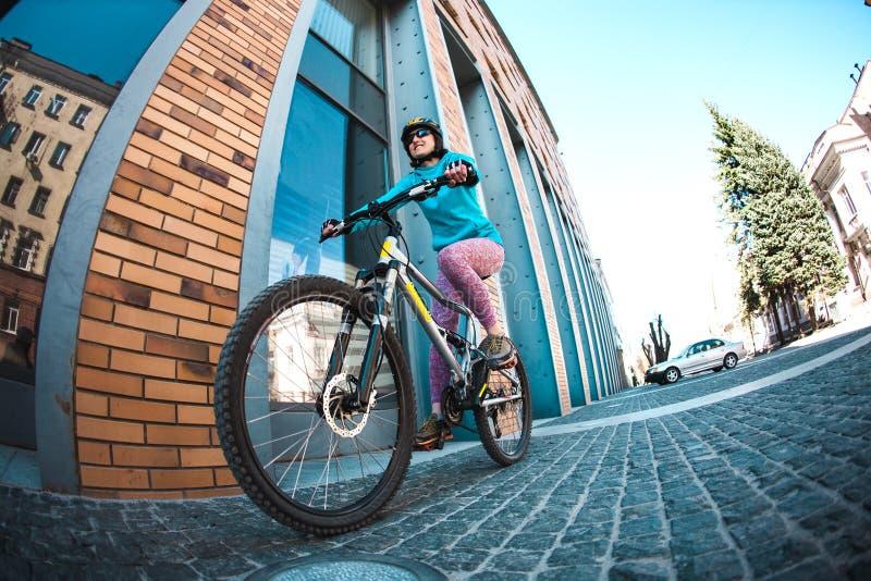 La fille monte un vélo autour de la ville photo stock
