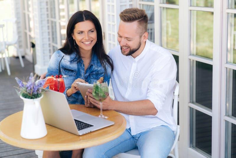 La fille montre à son ami une vidéo de sms sur le comprimé sur l'Internet Un couple se repose dans un café, embrassant photographie stock libre de droits