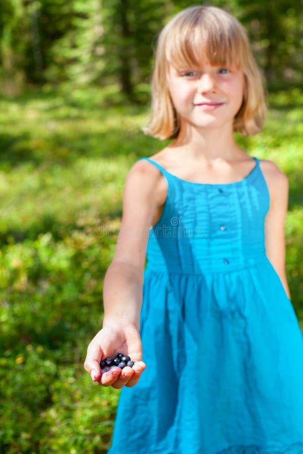 La fille montre les baies sélectionnées à un foyer peu profond de forêt d'été photographie stock libre de droits