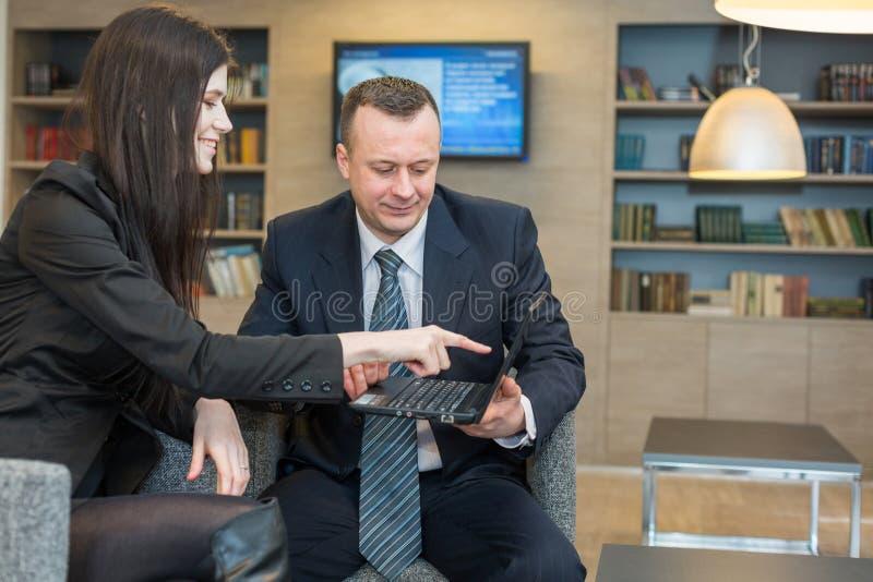 La fille montre un homme sur un ordinateur portable dans un costume photographie stock