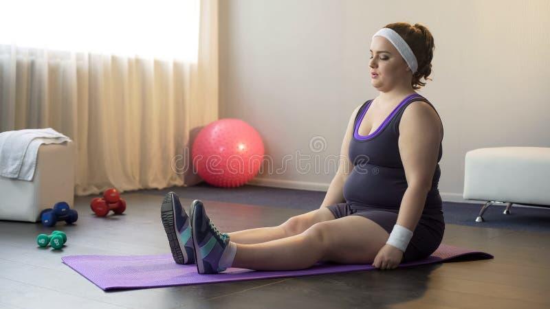 La fille motivée potelée faisant le sport s'exerce pour être en bonne santé et amincit, séance d'entraînement photos libres de droits