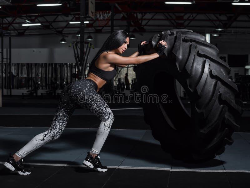 La fille musculaire puissante et attirante s'est engagée dans le crossfit, s'exerçant photo libre de droits
