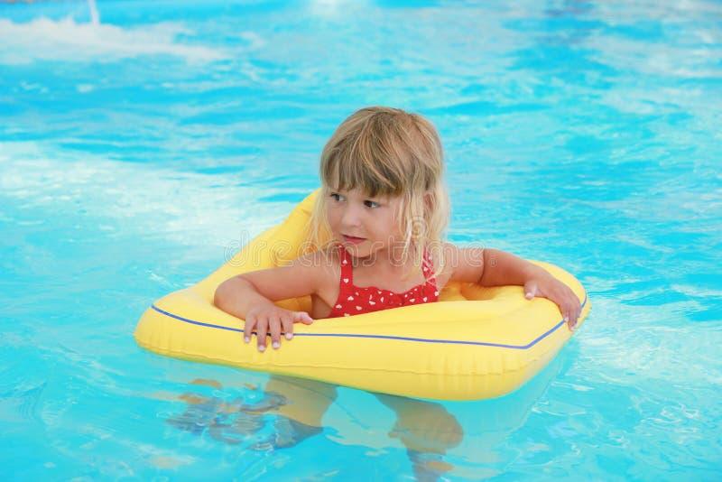 La fille nage dans une piscine avec un cercle photo stock for Apprendre a plonger dans une piscine
