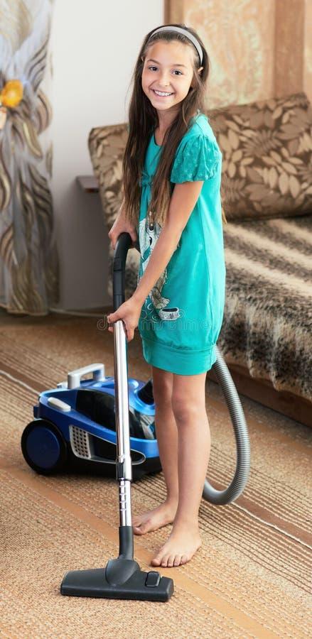 La fille nettoie à l'aspirateur image libre de droits