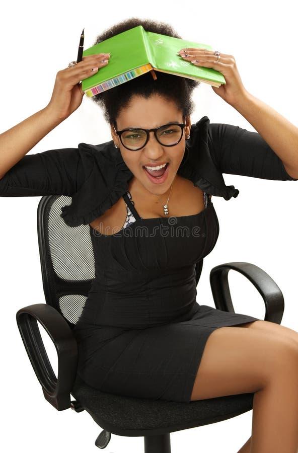 La fille noire dans la chaise de bureau dans la panique couvre la tête de noteb photographie stock libre de droits