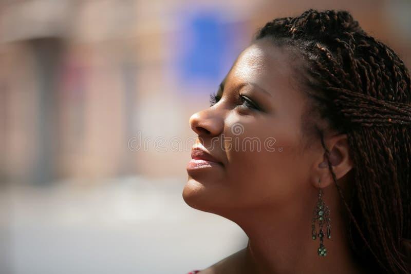 La fille noire sourit aux rayons de soleil photographie stock