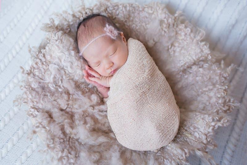 La fille nouveau-née dans un sommeil de cocon photos stock