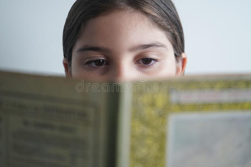 LA FILLE OBSERVE REGARDANT LE LIVRE photo stock