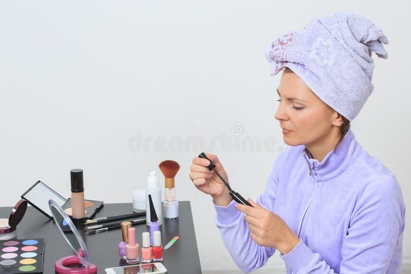 La fille obtient le mascara à la table avec le maquillage photos libres de droits