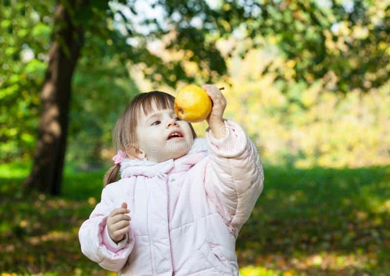 La fille offre une poire jaune mûre photographie stock libre de droits