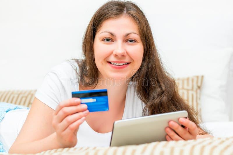 La fille ont le sort d'argent sur une carte de crédit image libre de droits