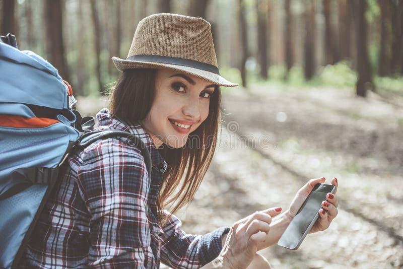 La fille optimiste tient le smartphone photographie stock