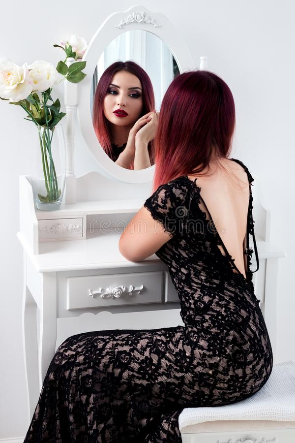 La fille ou la femme élégante avec le beau maquillage se tient sur le CCB blanc photos stock