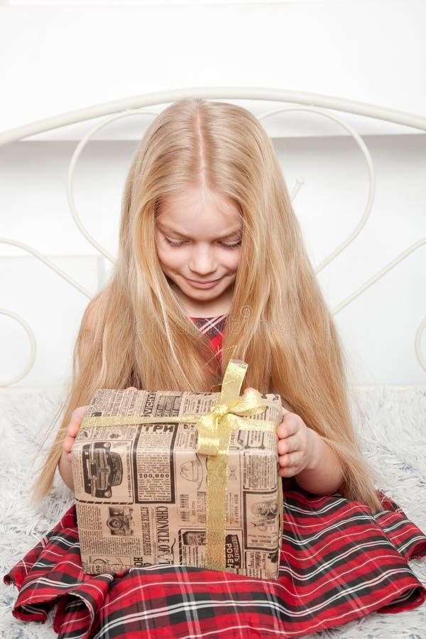 La fille ouvre le cadeau Concept de vacances photographie stock