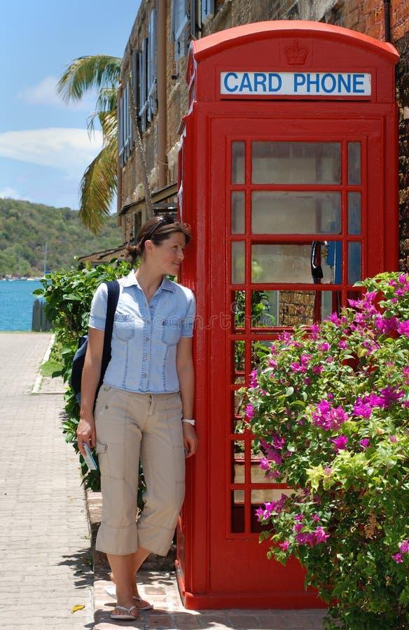 La fille par la cabine de téléphone image libre de droits