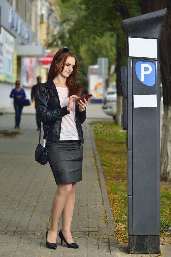 La fille paye se garer par l'intermédiaire de l'application mobile et le sourire rostov image stock
